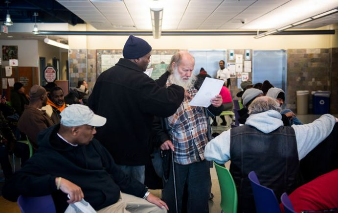 At Health Care for the Homeless, Simmons helps a man named Ethan. (Photo credit: Gabriella Demczuk for NPR.)