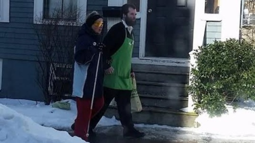 This photo of a Sobeys employee walking a 72-year-old customer home was posted to Facebook on Friday. (Terri Bordage Stevens/Facebook)